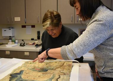 Mexican historian Lidia Gómez García examines a Latin American mapa with UO researcher Stephanie Wood.