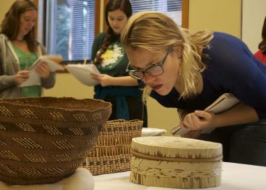 UO students examine a Native American basketry collection