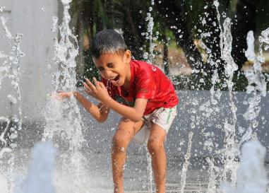 Child playing in a fountain