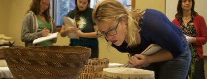 UO student examines a basket from the museum's collection.