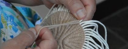 Close up of hands weaving a basket