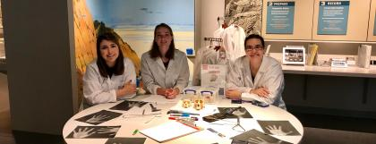 Three students in lab coats sitting around a table in the museum